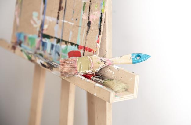 Pinsel zum malen auf einer staffelei auf unscharfem hintergrund