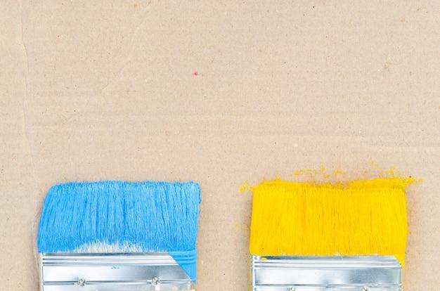 Pinselgebrauch für farbe blauer und gelber hintergrund für ausrüstung stock photography.