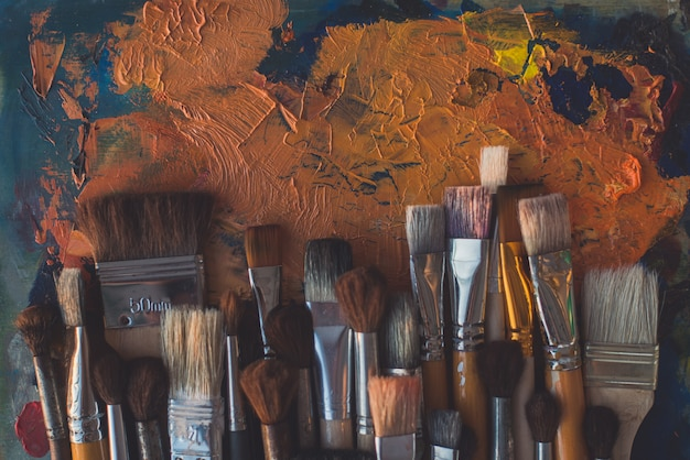 Pinselsammlung auf draufsicht der alten palette. mischen verschiedener ölfarben im kunststudio.