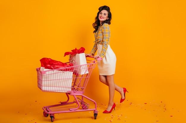 Pinup junge frau im weißen rock, der das einkaufen genießt. studioaufnahme des stilvollen mädchens, das auf gelbem hintergrund steht.