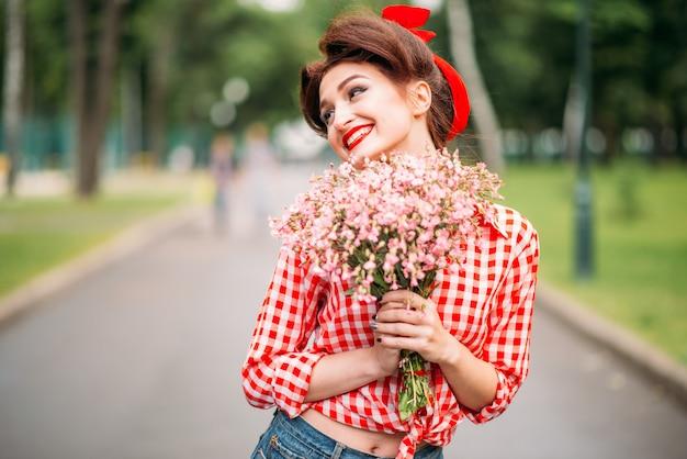 Pinup mädchen mit blumenstrauß, retro amerikanische mode. nette lächelnde frau im pin-up-stil