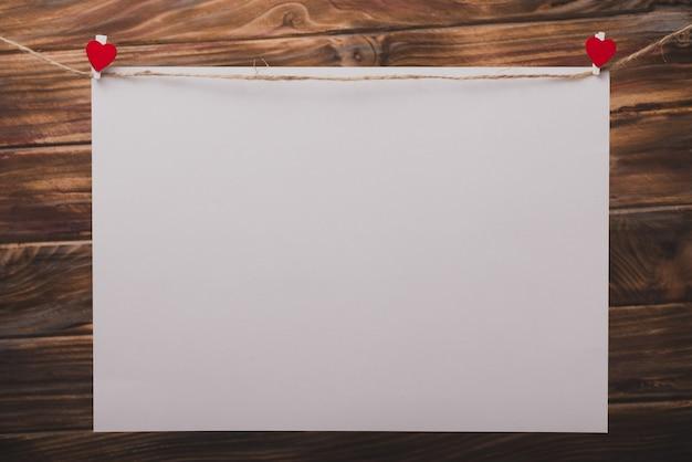 Pinzette mit einem herz auf einem großen papier