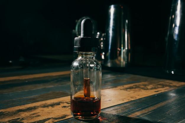 Pipette, die ätherisches öl in eine glasflasche auf hölzernem hintergrund fällt