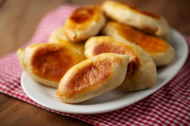 Pirozhki - kleine torte mit fleisch auf teller