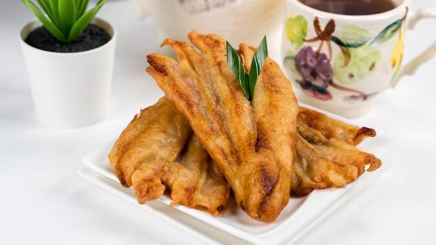 Pisang goreng oder bananenkrapfen indonesisch traditionell serviert in weißer platte mit tee