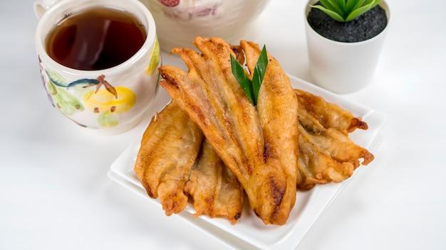 Pisang goreng oder bananenkrapfen indonesische traditionelle serviert in weißem teller mit tee