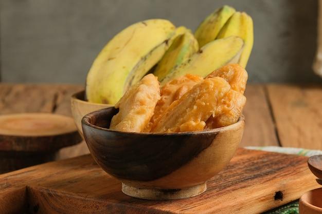 Pisang goreng serviert auf holztisch. ist beliebtes streetfood in südostasien, insbesondere in malaysia und indonesien. hergestellt aus gebratener banane mit süßem teig überzogen
