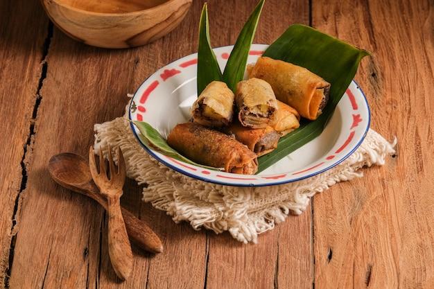 Piscok- oder bananenschokolade, traditionelle snacks aus indonesien. aus gebratener banane in frühlingsrollenhaut, gefüllt mit schokoladen- und käsescheiben.