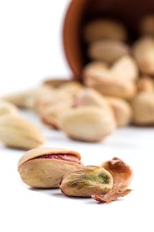 Pistazien- und cashewnüsse in tontöpfen auf weiß