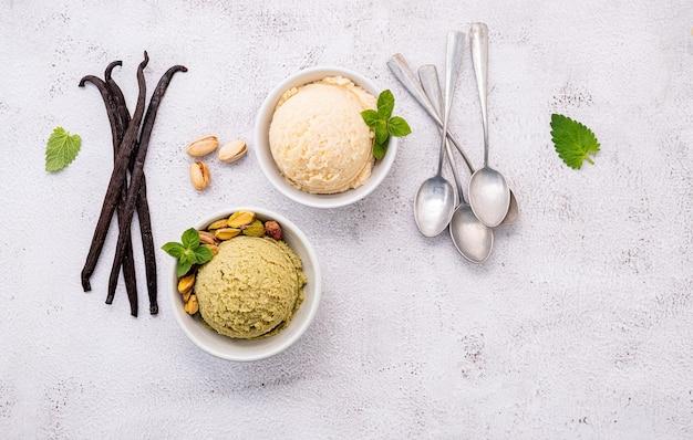 Pistazien- und vanilleeis in der schüssel mit gemischten nüssen auf weißem steinhintergrund