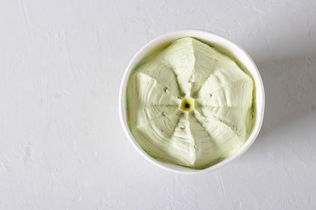 Pistazieneis in einem pappbecher auf hellem hintergrund. essen zum mitnehmen, ansicht von oben. platz kopieren