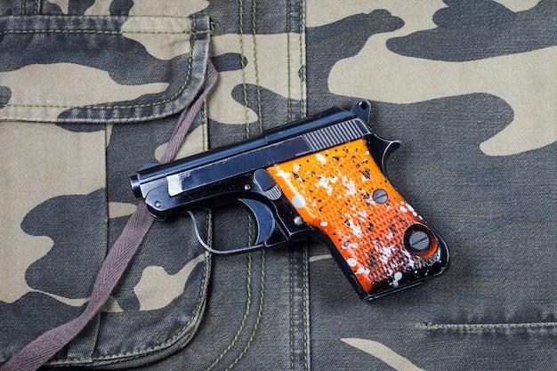 Pistole auf tarnhintergrund.
