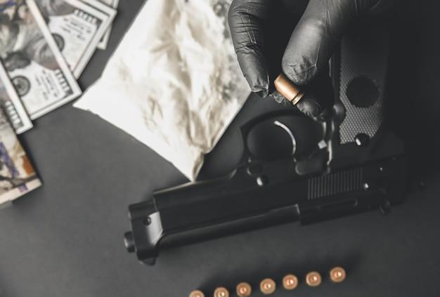 Pistole liegt auf dem tisch. mann in schwarzen handschuhen mit kugeln. illegaler drogenverkauf. kriminelle probleme. dollar.