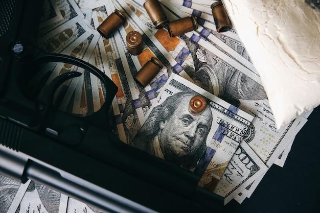 Pistole mit kugeln, die auf dem tisch liegen. kriminelle probleme. drogen und geld auf schwarzem hintergrund. illegaler verkauf. dollar.