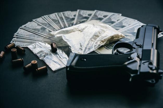 Pistole mit kugeln, die auf dem tisch liegen. kriminelle probleme. drogen und geld auf schwarzem hintergrund. illegaler verkauf.
