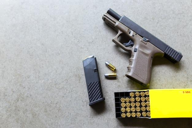 Pistole mit munition auf einem tisch. 9 mm pistole und kugel für die verteidigung.