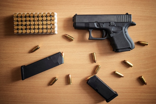 Pistole mit munitionskiste und kugeln auf holzwand
