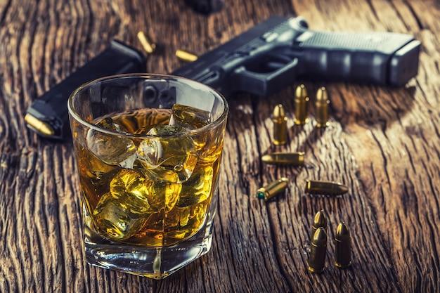 Pistole und alkohol. 9-mm-pistole und becher whisky cognac oder brandy.