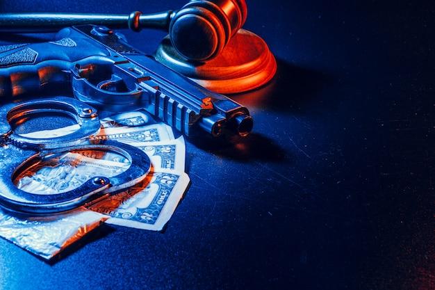 Pistole und richterhammer auf dem tisch. verbrechen, raub, angriffskonzept
