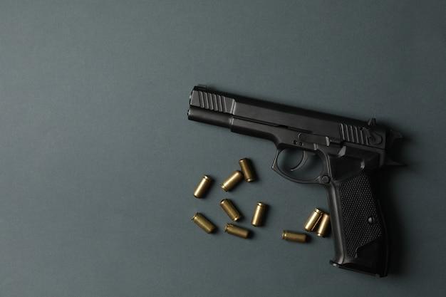 Pistole und traumatische kugeln auf dunkelgrau. selbstverteidigungswaffe