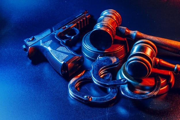 Pistolen- und richterhammer auf dem tisch. verbrechen, raub, angriffskonzept