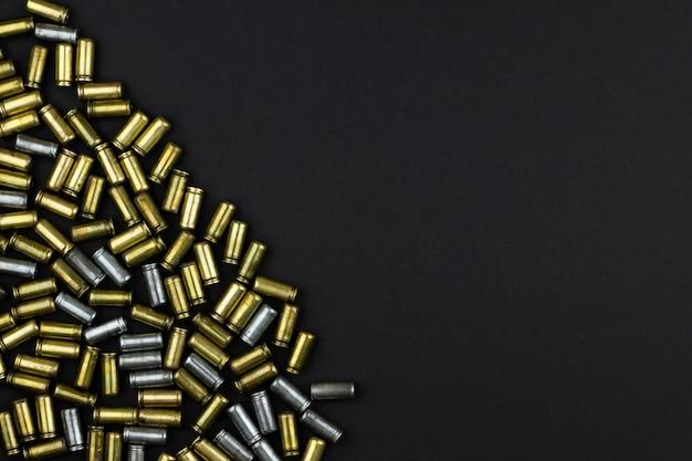 Pistolenpatronen sind auf einer schwarzen oberfläche verstreut