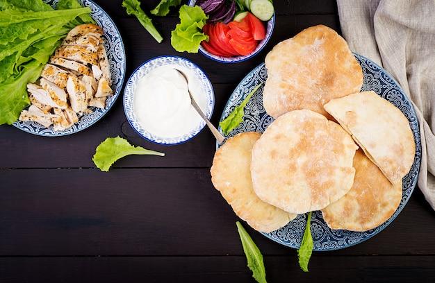 Pita angefüllt mit huhn, tomate und kopfsalat auf hölzerner, nahöstlicher küche, draufsicht