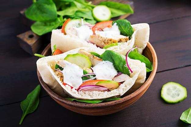 Pita gefüllt mit huhn, tomate, gurke und spinat auf holzoberfläche