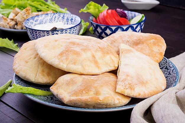 Pita gefüllt mit huhn, tomate und kopfsalat auf hölzerner, nahöstlicher küche.