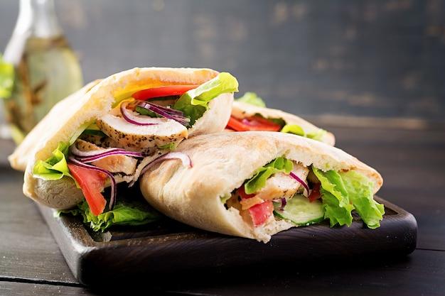 Pita gefüllt mit huhn, tomate und salat auf holztisch. nahöstliche küche.