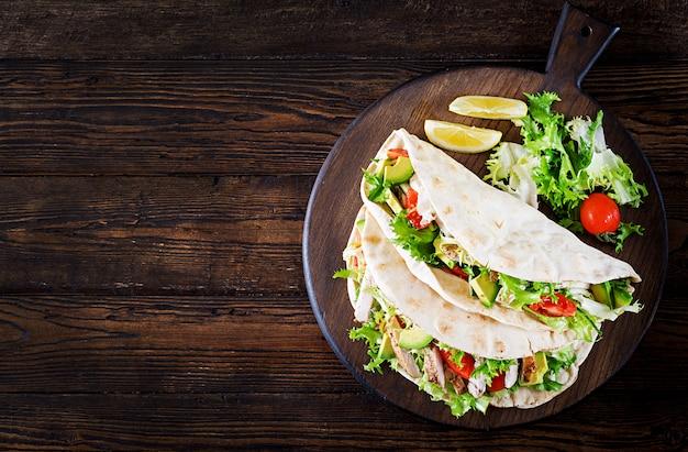Pitabrotsandwiche mit gegrilltem hühnerfleisch, avocado, tomate, gurke und kopfsalat dienten auf holz