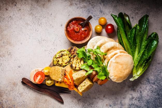 Pitas, gemüsepastetchen, tomatensauce und gegrilltes gemüse auf hölzernem brett, draufsicht. kochen des gesunden vegetarischen nahrungsmittelkonzeptes.
