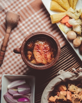 Piti in einem tontopf mit zwiebeln