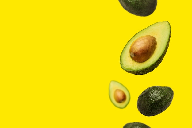 Pitted avocado und ganze avocado fliegen in der luft auf einem gelben