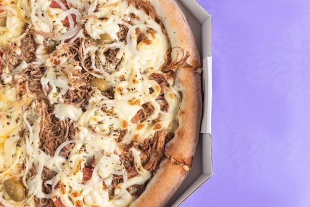 Pizza auf dem tisch in lila farbe