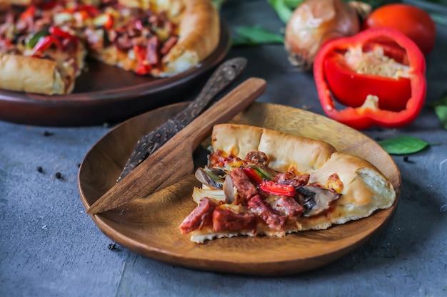 Pizza auf dem tisch mit zutaten herum