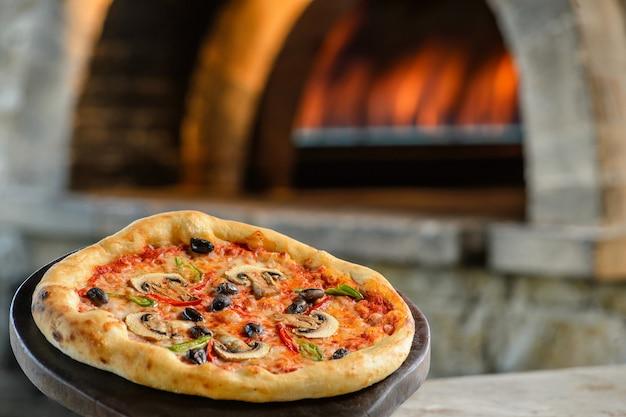Pizza auf dem tisch und echtes feuer dahinter