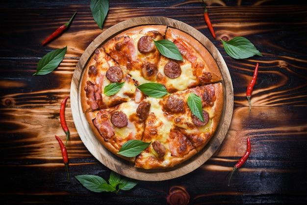 Pizza auf draufsicht des hölzernen behälter- und paprikabasilikumblattes