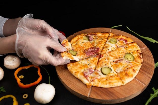 Pizza auf einem holzständer auf einer schwarzen oberfläche mit behandschuhten händen nehmen sie ein stück pizza