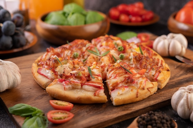 Pizza auf einen holzteller gelegt.