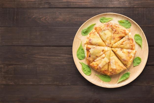 Pizza auf hölzernem hintergrund. kopieren sie platz für ihren text