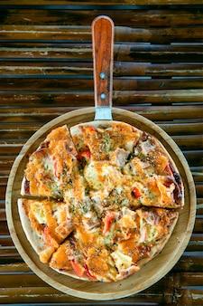 Pizza auf holzteller auf bambustisch.