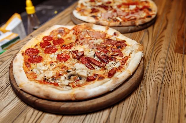 Pizza auf holztisch draufsicht. fast food. post blog social media. mit kopierplatz. pizza essfertig.