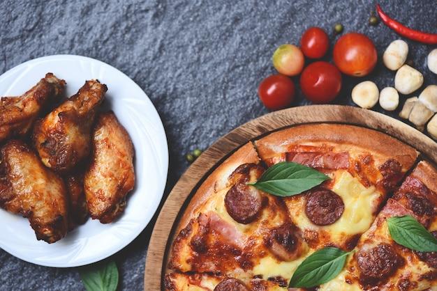 Pizza auf köstlichem geschmackvollem italienischem traditionellem und gebackenem hühnerflügel-bbq-grill des hölzernen behälters draufsicht