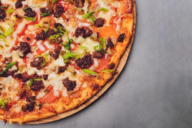 Pizza auf papier auf einem holzbrett. pizza auf einer schwarzen tischnahaufnahme. gesundes warmes essen.