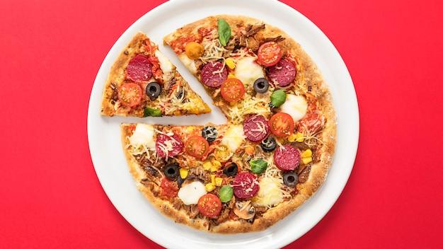 Pizza auf teller in scheiben geschnitten