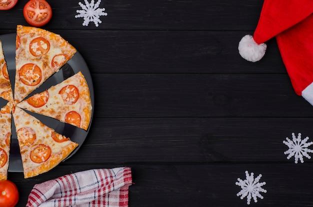 Pizza bestellen für den weihnachtstag. scheiben pizza mit käse und tomaten auf einem schwarzblech mit bestandteilen auf einem schwarzen hintergrund.