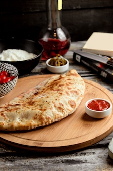 Pizza calzone auf holzbrett