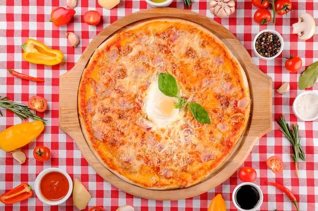 Pizza carbonara mit speck, ei, parmesan, frischem basilikum und tomatensauce auf einem holzbrett