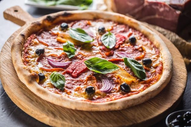 Pizza diavolo traditionelles italienisches essen aus würzigen salami-peperoni-chili-zwiebel-oliven und basilikum.